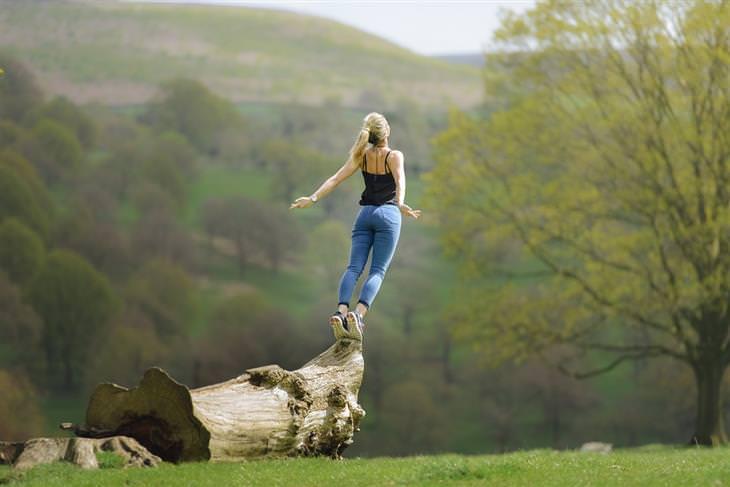 מדיטציית בוקר: אישה עומדת על גזע עץ ומותחת את גופה