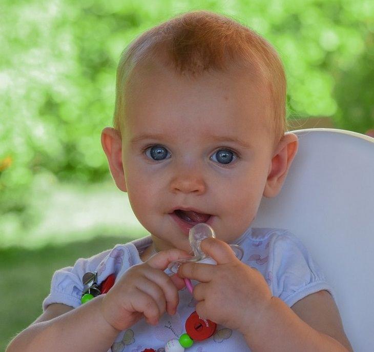 האם לתת מוצץ לילדים: תינוקת מחייכת עם מוצץ ביד