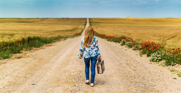 עקרונות לחיים טובים מפי ויין דיר: אישה הולכת לבדה בשביל עפר ארוך עם מזוודה בידה