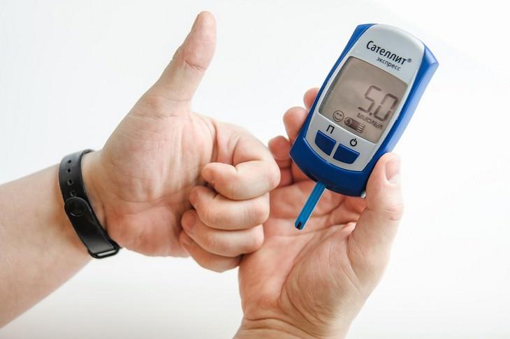 יתרונות בריאותיים של פיטאיה: גבר מחזיק מכשיר לבדיקת רמת סוכר בדם ומסמן אגודל כלפי מעלה