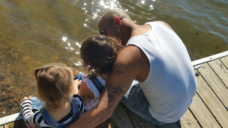 טיפים לפרידה בזוגיות: גבר יושב עם 2 ילדים על מזח מעל מים
