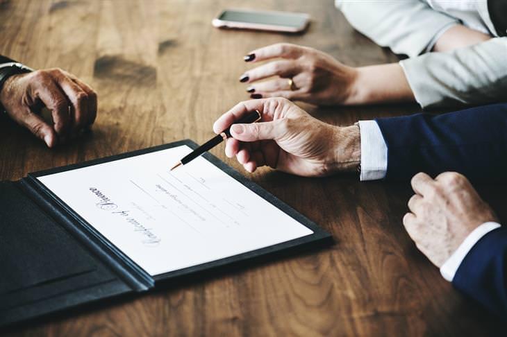 טיפים לפרידה בזוגיות: שולחן שסביבו יושבים אנשים ויד אחת אוחזת עט מעל חוזה