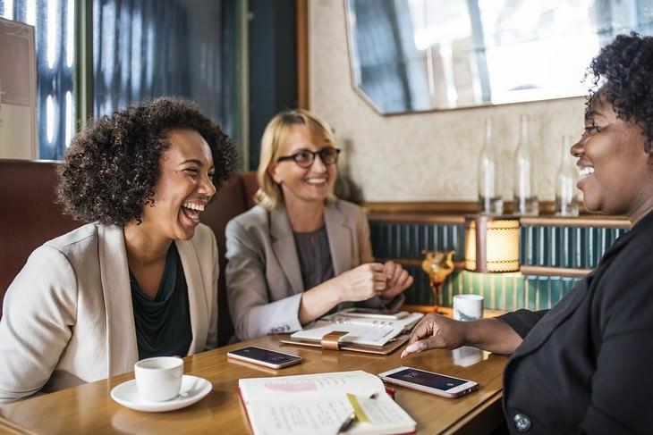 טקטיקות לשיפור התקשורת: שלוש נשים יושבות ליד שולחן בבית קפה וצוחקות