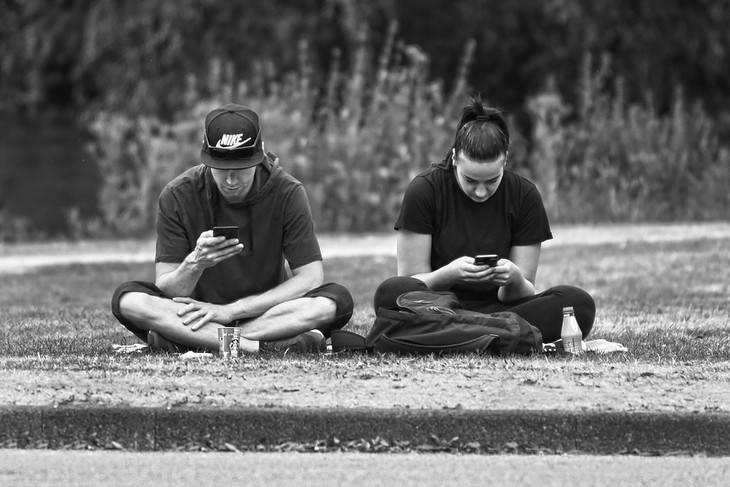 טקטיקות לשיפור התקשורת: גבר ואישה יושבים על דשא ומשחקים כל אחד בפלאפון שלו