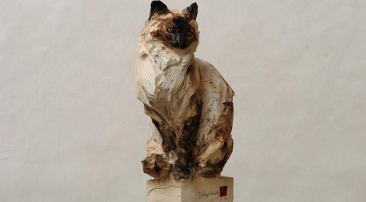אמן שמפסל בעץ בעזרת מסור: פסל חתול