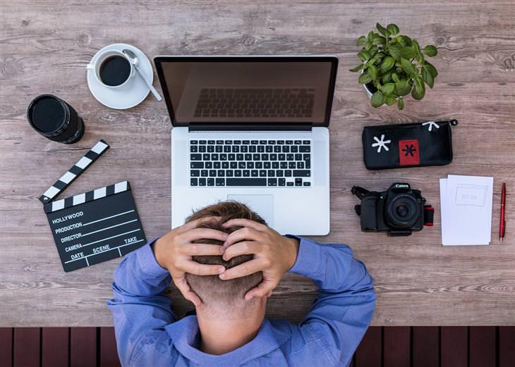 איך להתגבר על תשישות מנטלית: איש יושב מול מחשב נייד ואוחז בראשו