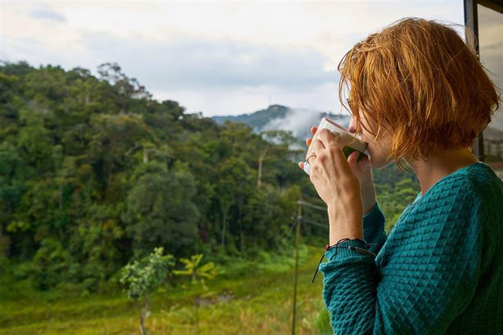 איך להתגבר על תשישות מנטלית: אישה שותה מכוס מול נוף ירוק