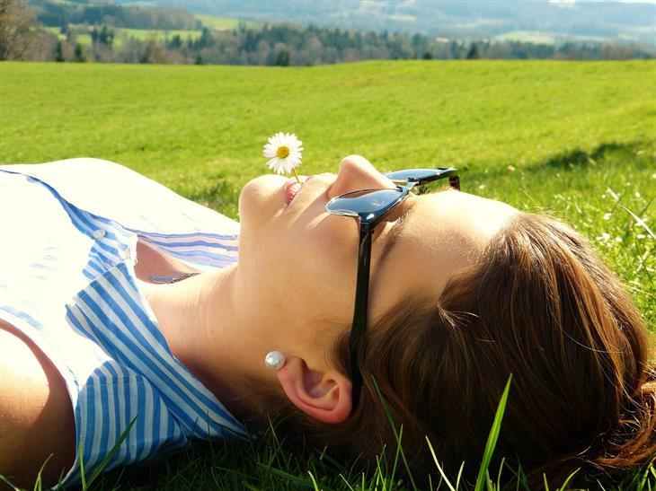 איך להתגבר על תשישות מנטלית: אישה שוכבת על דשא עם פרח בפיה