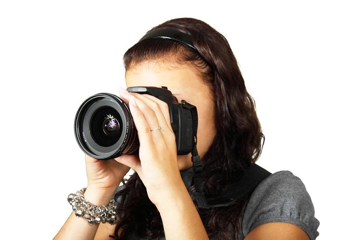 טיפים לקניית מצלמה דיגיטלית: אישה מצלמת במצלמה דיגיטלית