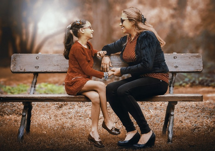 סודות למשפחה מאושרת: אימא ובת יושבות על ספסל וצוחקות