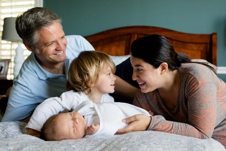 סודות למשפחה מאושרת: שני הורים ושני ילדים ביחד במיטה גדולה מחייכים