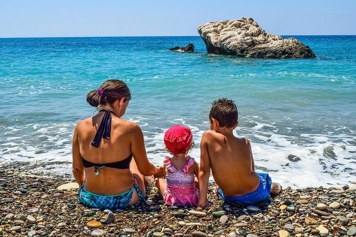 סודות למשפחה מאושרת: אימא ושני ילדים יושבים על חוף הים