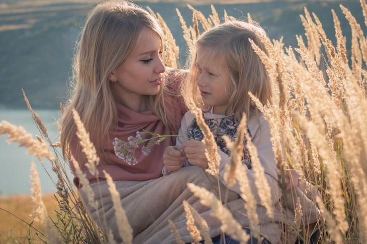 סודות למשפחה מאושרת: אמא ובת יושבות בשדה ומדברות
