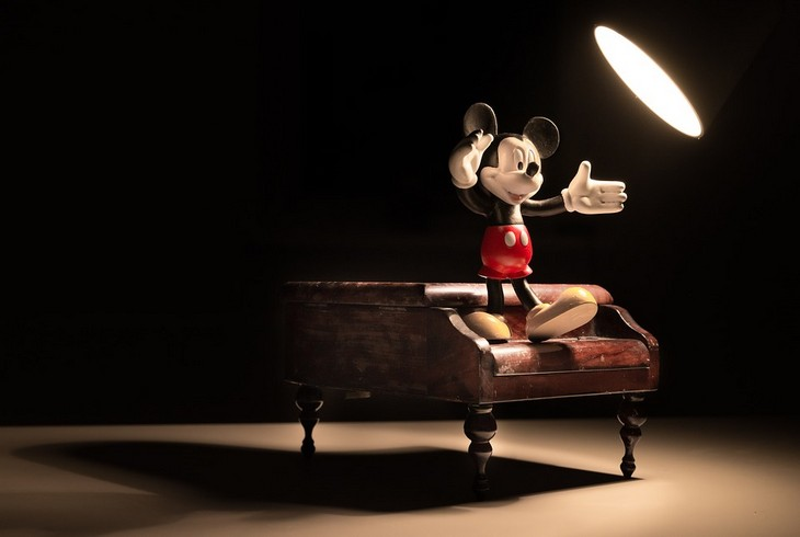 איך להחזיר את האמונה העצמית: בובת מיקי מאוס עומדת על פסנתר קטן ומוארת בנורת שולחן