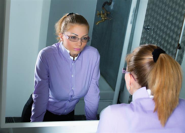 איך לשלוט בכעס: אישה מסתכלת על עצמה במראה