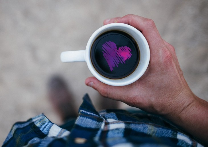 איך להחזיר את האמונה העצמית: יד מחזיקה כוס קפה ובתוכה מצוייר לב