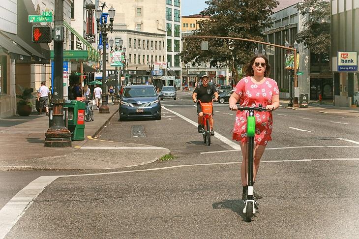 חוקים ותקנות לרכיבה על קורקינט ואופניים חשמליים: אישה רוכבת על קורקינט חשמלי ומאחוריה גבר רוכב על אופניים