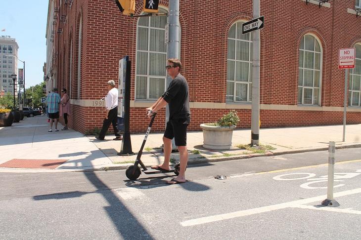 חוקים ותקנות לרכיבה על קורקינט ואופניים חשמליים: גבר עומד על קורקינט חשמלי בשביל מסומן לרכיבת אופניים