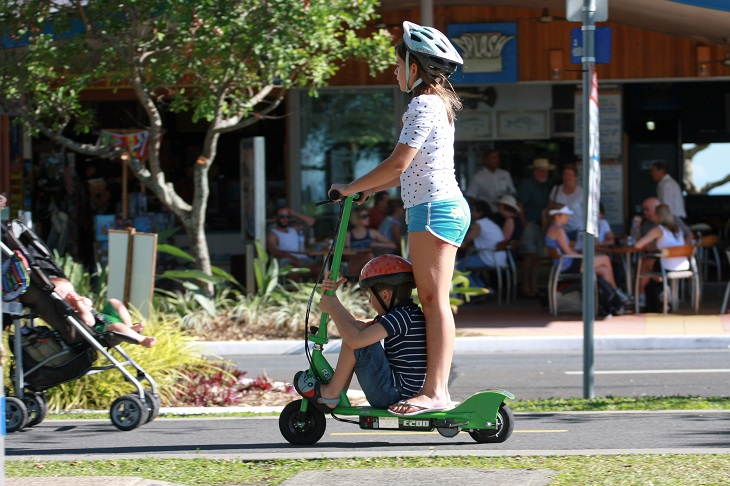 חוקים ותקנות לרכיבה על קורקינט ואופניים חשמליים: ילדה מרכיבה ילד על קורקינט חשמלי