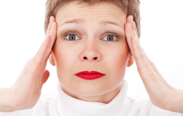 לפני שאתם נוטלים משככי כאבים: אישה מחזיקה את ראשה בין ידיה