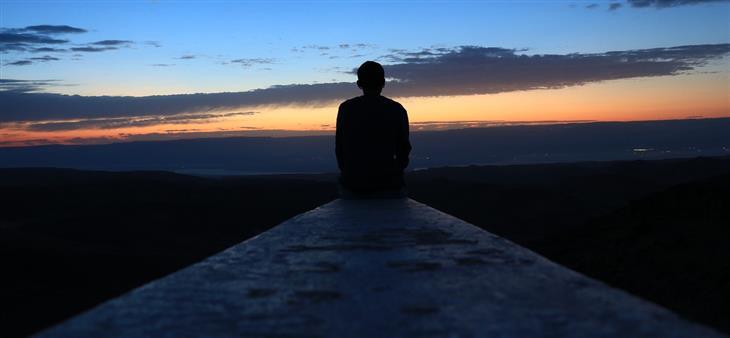 תזכורות שישנו את נקודת מבטכם בנוגע לעצמכם: איש יושב מול שקיעה