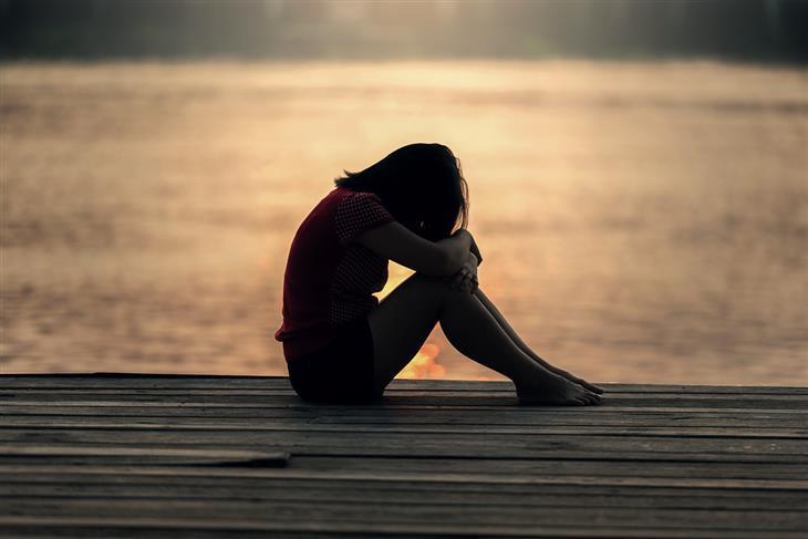 תזכורות שישנו את נקודת מבטכם בנוגע לעצמכם: אישה יושבת על מזח וראשה מורכן על ברכיה, בין ידיה
