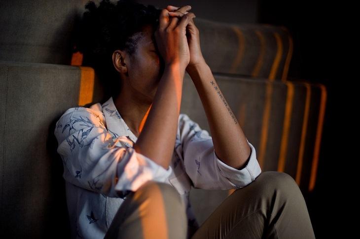 הסיבות לדחיינות: אישה יושבת על הרצפה ונשענת על ספה כאשר ידיה מכסות את פניה