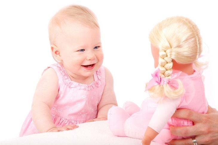 8 סימנים שתינוקכם בריא: תינוקת מצחקקת לעבר הבובה שלה