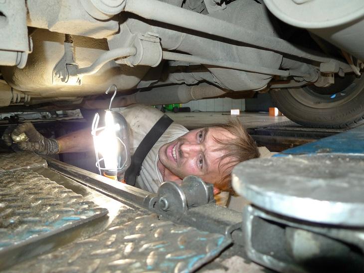 דברים שמזיקים לרכב שלכם: מכונאי בודק עם פנס את החלק התחתון של רכב