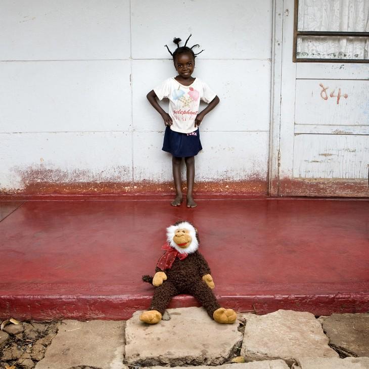 ילדים עם צעצועיהם: ילדה עומדת ולרגליה בובת קוף