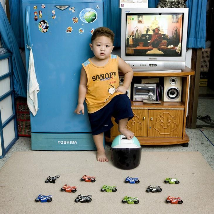 ילדים עם צעצועיהם: ילד עם צעצועי אופנועים שם את רגלו על קסדה