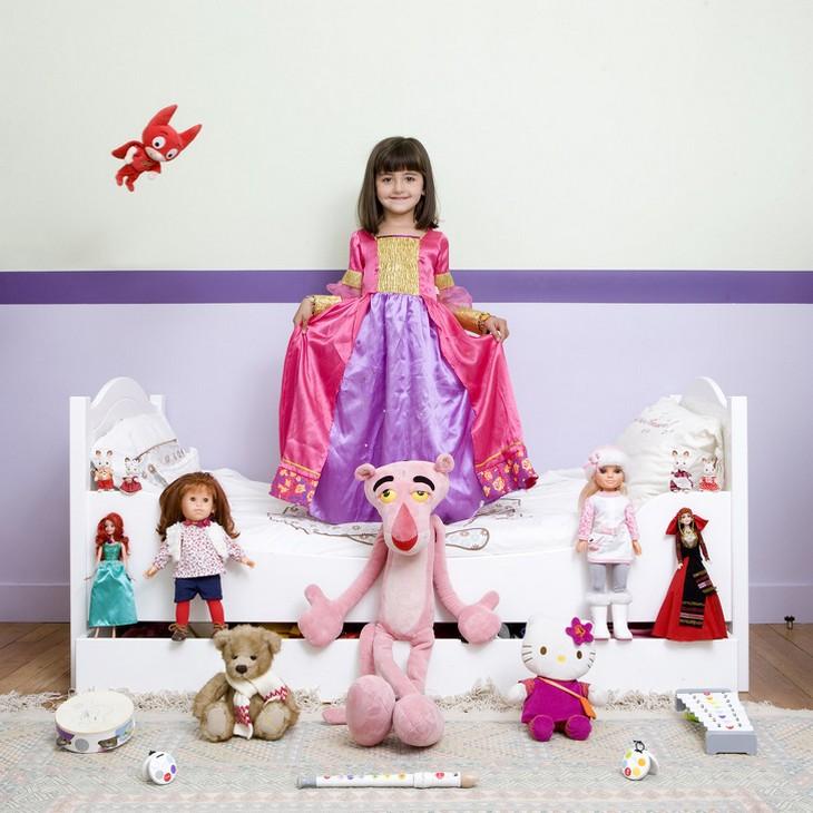 ילדים עם צעצועיהם: ילדה עומדת על מיטה ולרגליה כל הבובות שלה