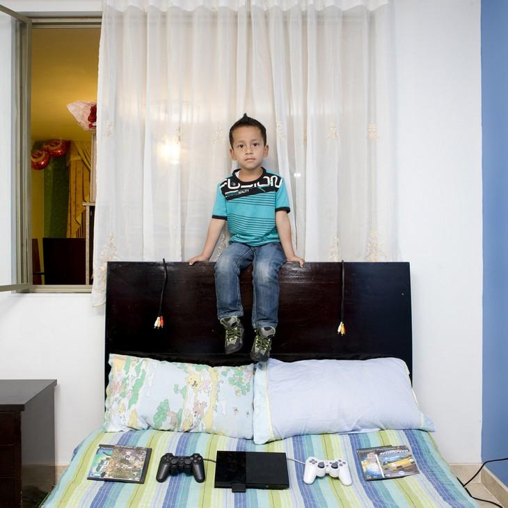 ילדים עם צעצועיהם: ילד יושב על גב מיטה ועליה מונח מכשיר סוניפלייסטישן