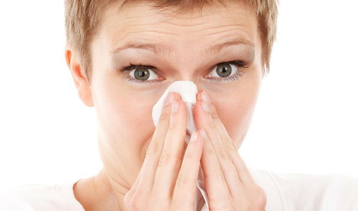 סיבות לכך שלא מומלץ לישון עם חיית המחמד: אישה מקנחת את האף