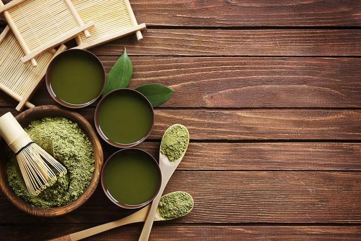 תכשירים קוסמטיים טבעיים מבוססי מלפפון: שולחן עץ ועליו מונחים שלוש קעריות של משחות ירוקות וקערה אחת עם אבקה ירוקה