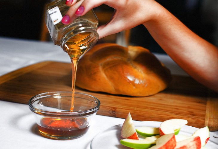 ברכה לשנה החדשה: יד מוזגת דבש ממיכל לקערה