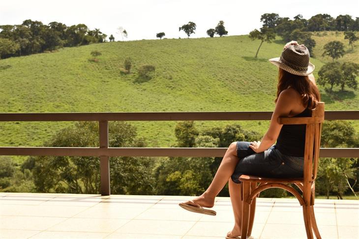 טכניקות מיינדפולנס: אישה יושבת על כיסא במרפסת מול נוף ירוק