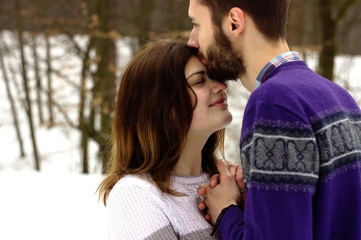 ירח דבש בחורף: זוג צעיר מחובק על רקע שלג