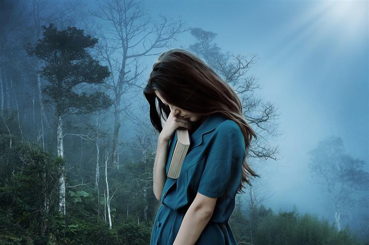 סיבות לדכדוך לא מוסבר: אישה מחזיקה ספר ועומדת מול יער חשוך