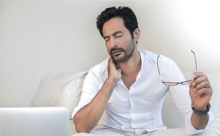 איך למנוע כאבי צוואר שנוצרים בשינה: איש אוחז בצווארו