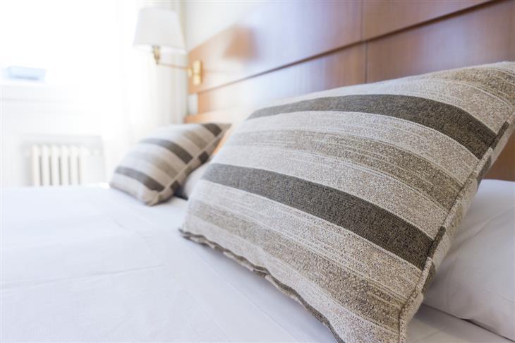 איך למנוע כאבי צוואר שנוצרים בשינה: כריות על מיטה