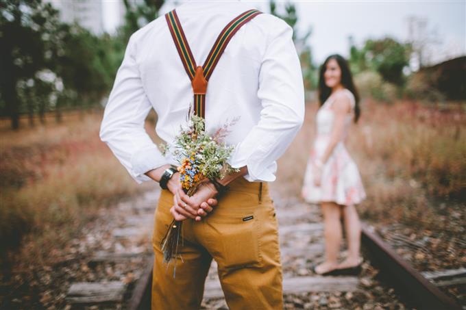 בחן את עצמך: גבר מחזיק פרחים מאחורי גבו ומולו אישה