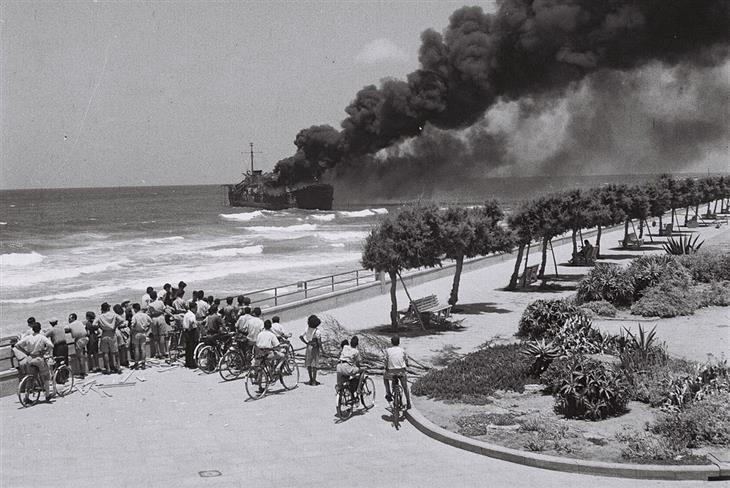 תמונות יפות מויקיפדיה: קהל של סקרנים בחופי תל אביב מביטים על אוניית הנשק הבוערת אלטלנה