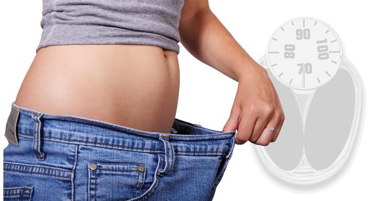 דברים שעליכם לדעת לפני שאתם מתחילים דיאטה: אישה מחזיקה מול הבטן שלה מכנס שגדול עליה ומאחוריה משקל