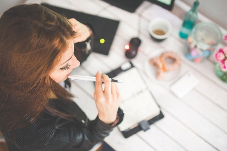 שאלות לבחינת יכולות קוגניטיביות: אישה יושבת לצד שולחן ומחזיקה בפיה עט