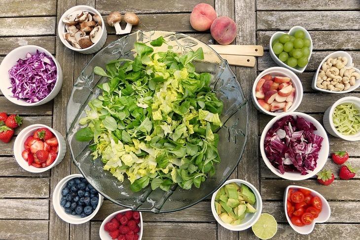 10 דרכים יצירתיות לגרום לילדיכם לאכול מזון בריא: קערה גדולה עם חסה קצוצה ומסביבה קעריות עם פירות ירקות ואגוזים