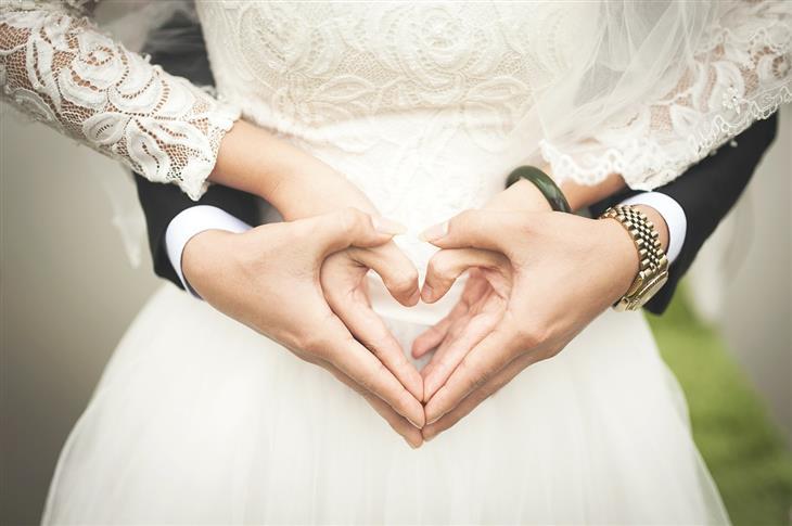 טיפים לזוגיות מוצלחת ומאושרת: זוג בבגדי חתונה אוחזים ידיים בצורת לב