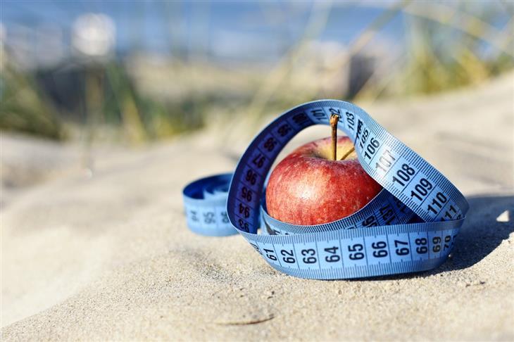 דברים שעליכם לדעת לפני שאתם מתחילים דיאטה: תפוח עטוף בסרט מדידה על חול