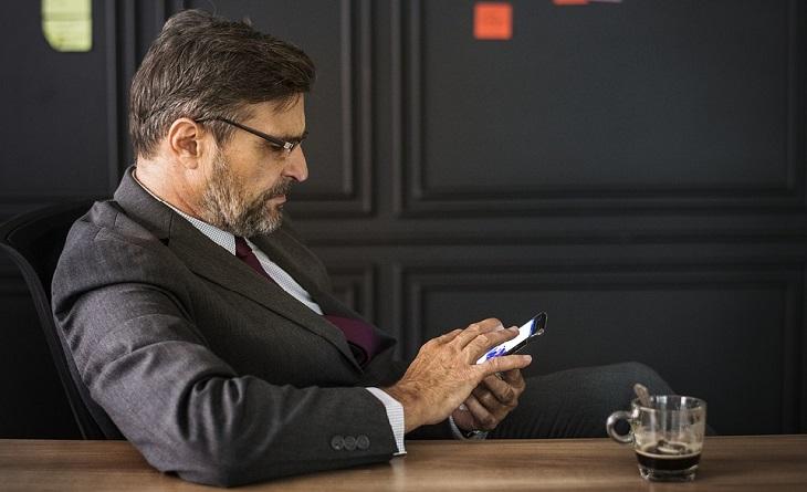 סימנים לבגידה: גבר מבוגר משתמש בטלפון סלולרי