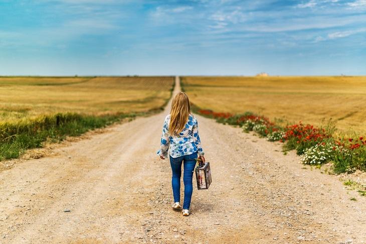 9 פעולות שצריך להפסיק לפחד מהן: אישה צועדת בדרך לא סלולה, מזוודה קטנה בידה